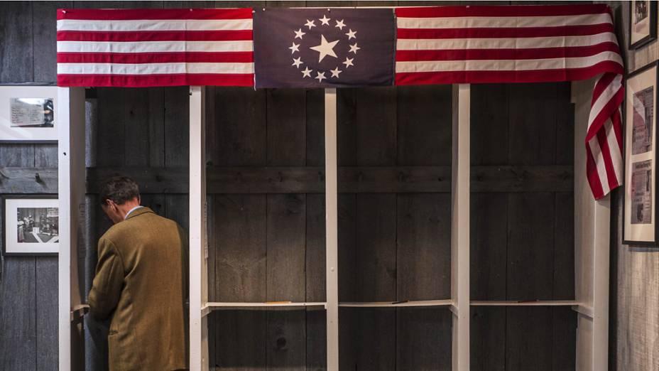 Homem se prepara para lançar seu voto dentro de uma cabine de votação em Dixville Notch, New Hampshire