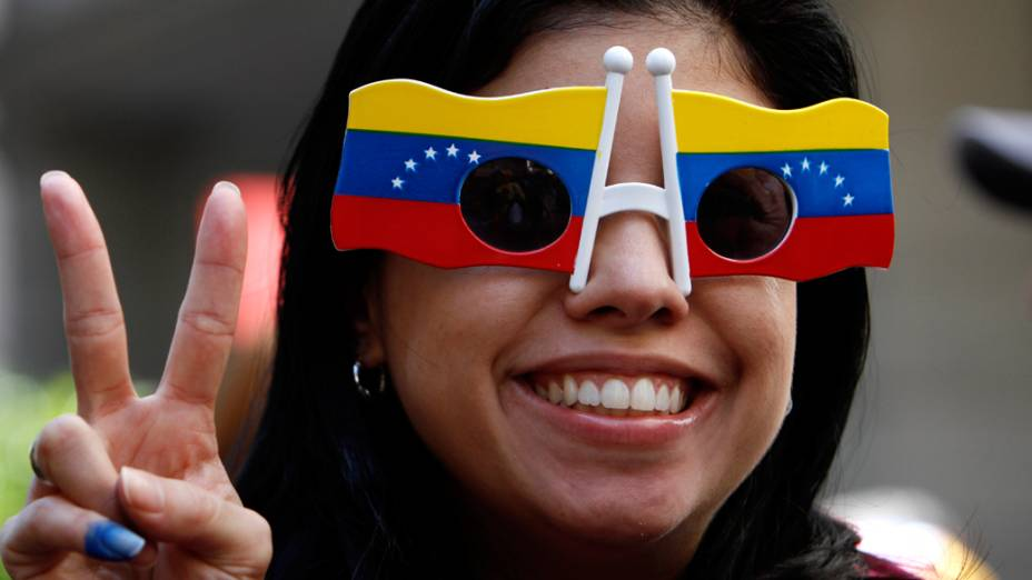 Cidadã venezuelana que vive no México posa usando óculos com as cores da bandeira do seu país próximo ao consulado da Venezuela no México, durante as eleições presidenciais