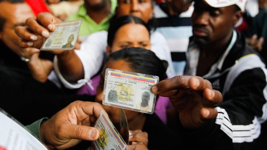 Cidadãos venezuelanos exibem documentos de identidade durante eleições presidenciais em Caracas