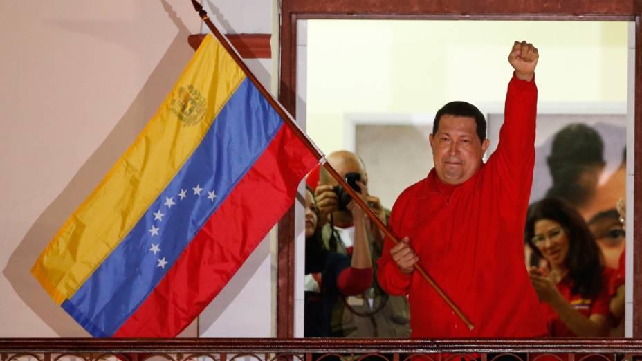 Hugo Chávez segura a bandeira venezuelana ao falar para apoiadores em Caracas depois de ser reeleito em outubro de 2012