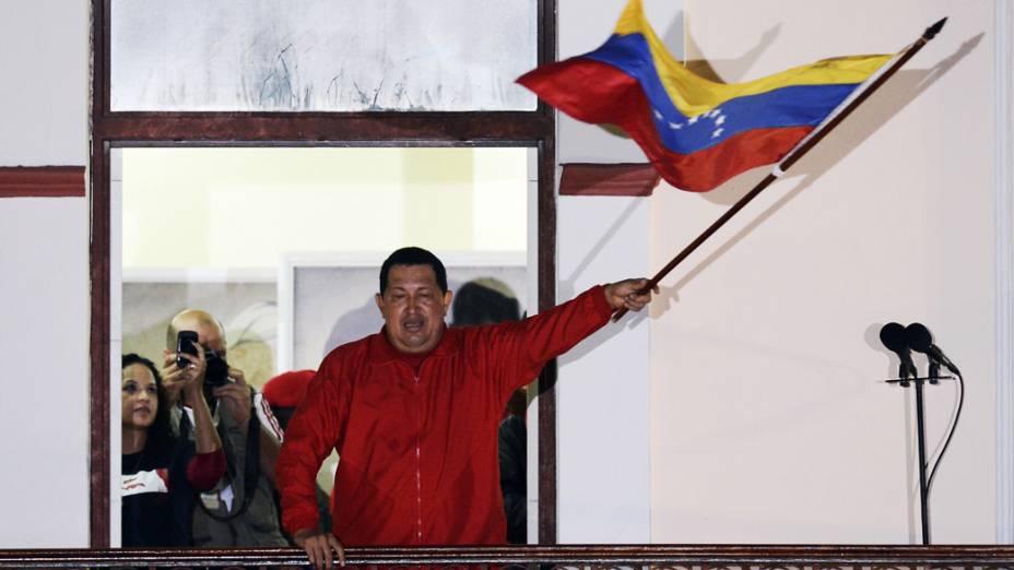 Hugo Chávez segura a bandeira venezuelana ao falar para a milhares de pessoas que se reuniram em Caracas após a confirmação da reeleição do presidente