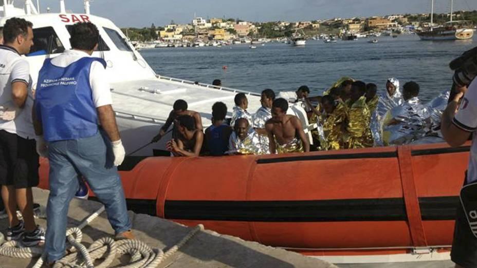 Equipes de resgate levam sobreviventes de naufrágio para a costa da Ilha de Lampedusa, na Itália