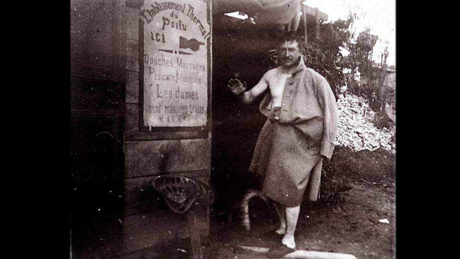 """Soldado francês é fotografado depois do banho em retaguarda de front em local não identificado na França. A placa diz: 'Complexo termal de Poilu. Chuveiros, massagens, pedicure, manicure"""""""