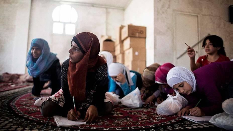 Filhos de refugiado da Síria assistem à aula em uma escola improvisada na cidade de Azaz, na fronteira com a Turquia