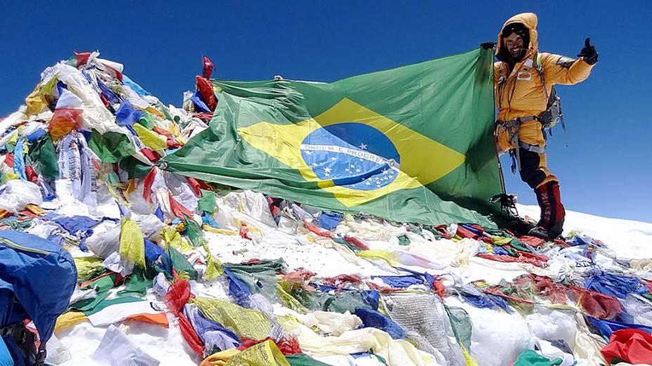 O alpinista Rodrigo Raineri segura a bandeira do Brasil no topo do Everest