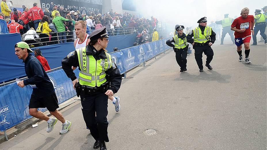Policiais e pessoas correm após as duas explosões na maratona de Boston