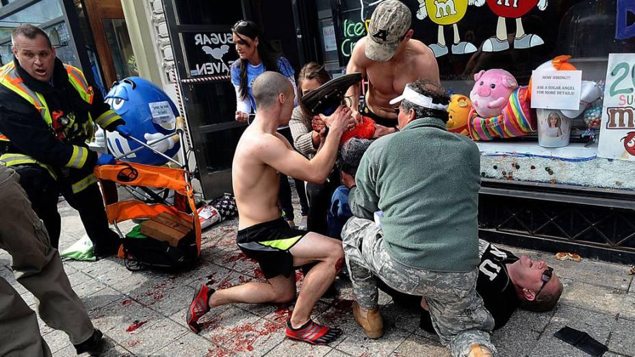 Espectadores atendem a um homem ferido após sequência de explosões durante a Maratona de Boston, em Massachusetts