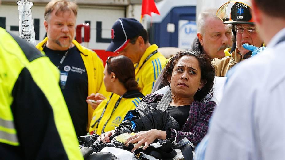 Mulher é levada até uma ambulância por equipes de resgate, após duas explosões na maratona de Boston