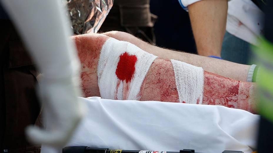 Homem ferido é socorrido em uma ambulância estacionada em uma tenda médica localizada próximo ao local de chegada da Maratona de Boston