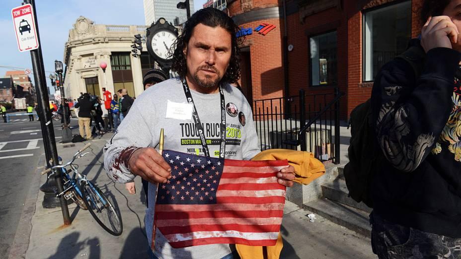 Homem mostra uma bandeira dos Estados Unidos manchada de sangue, após duas explosões na maratona de Boston
