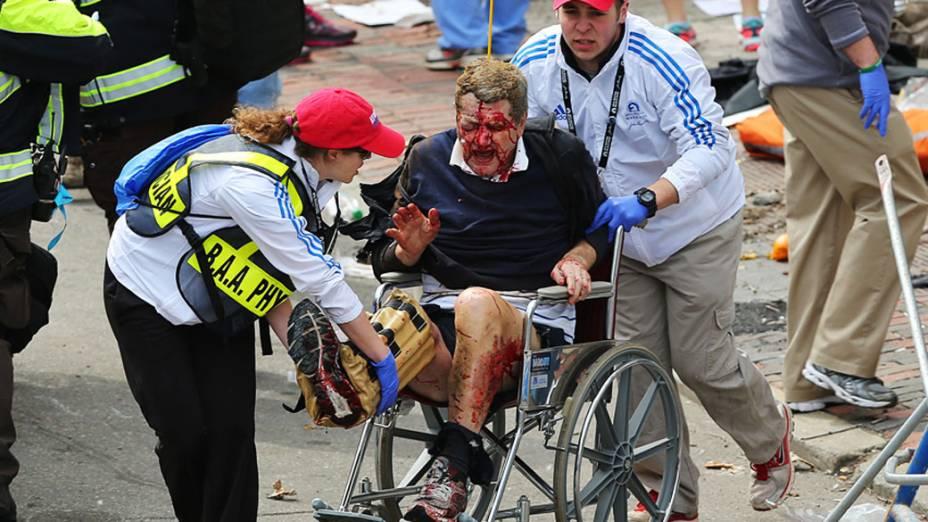 Homem ferido na explosão perto da linha de chegada da Maratona de Boston é retirado em uma cadeira de rodas