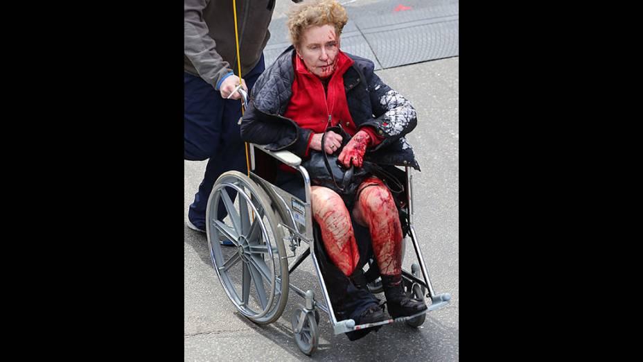 Mulher ferida recebe atendimento de equipes de resgate, após duas explosões na maratona de Boston