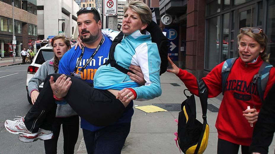 Mulher é carregada por um homem, após duas explosões na maratona de Boston
