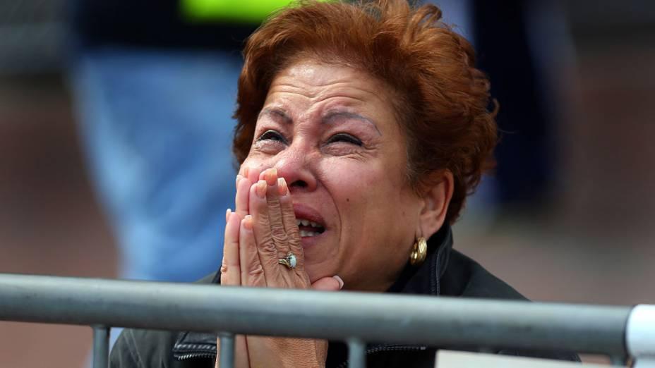 Mulher se ajoelha e reza no local da primeira explosão na Boylston Street, perto da linha de chegada da Maratona de Boston