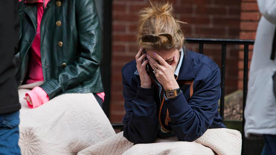Mulher chora no local da primeira explosão na Boylston Street, perto da linha de chegada da Maratona de Boston