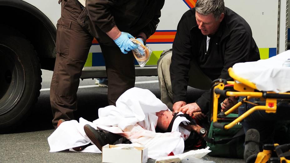 Ferido durante a explosão recebe primeiros socorros no local onde acontecia a maratona