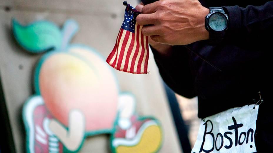 Homem segura a bandeira dos Estados Unidos no local de explosão perto da linha de chegada da Maratona de Boston