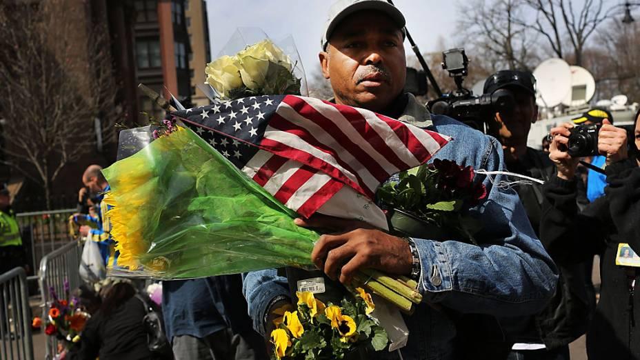 Homem leva flores e bandeira para o memorial das vítimas da explosão na maratona de Boston