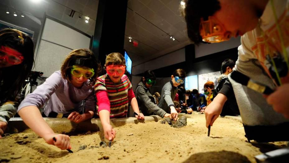 """<p>Visitantes aprendem a escavar fósseis durante a exposição """"Os Maiores Dinossauros do Mundo"""", em Nova York</p>"""