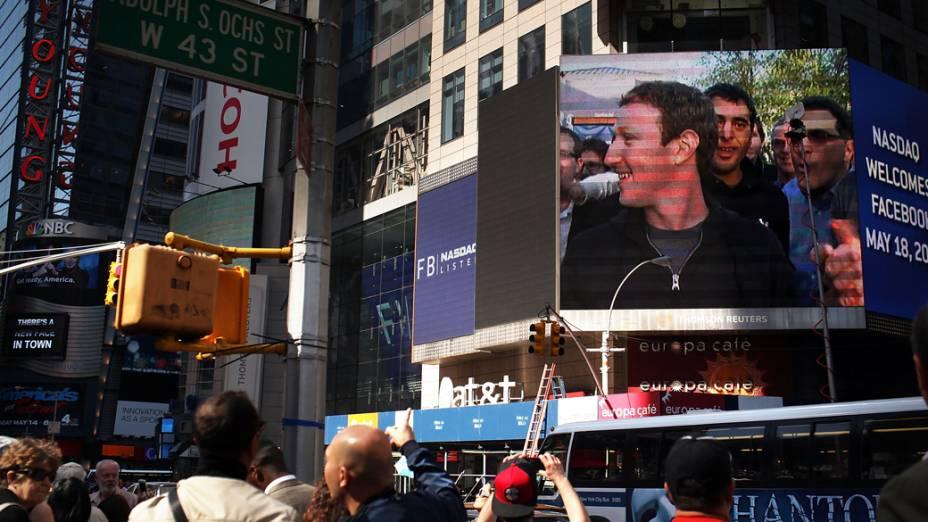 O fundador do Facebook aparece em telão em Nova York e pedestres registram momento tirando fotografias na Times Square