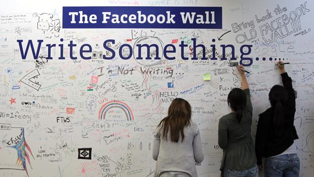 Funcionários do Facebook escrevem em um mural na sede da empresa em Palo Alto, Califórnia
