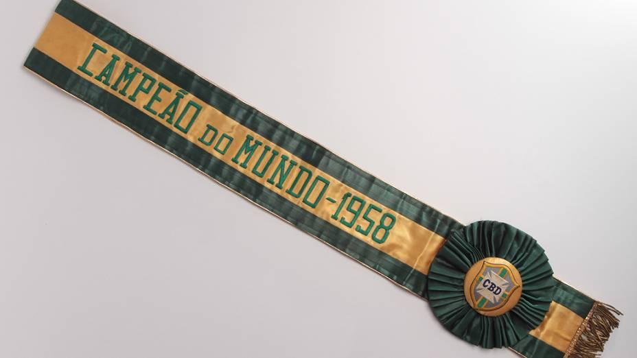 Objetos do acervo pessoal de Pelé no livro As joias do rei, de Celso de Campos Jr. Na imagem, a faixa do primeiro titulo mundial do Brasil em 1958