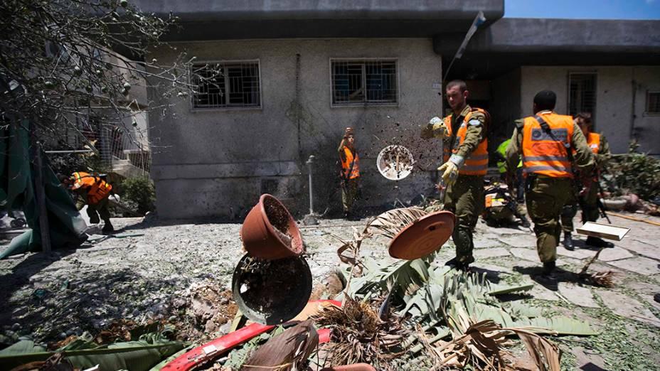 Em Israel, soldados andam em meio aos escombros de uma casa destruída porum foguete disparado por militantes palestinos na Faixa de Gaza, em 15/07/2014