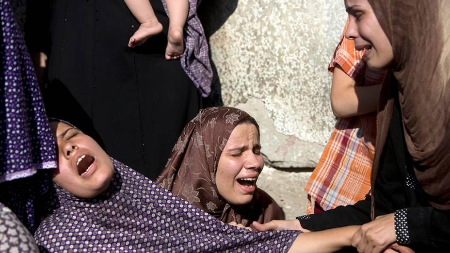 Parentes de quatro rapazes mortos em bombardeio naval israelense são vistas durante funeral na cidade de Gaza. A intensificação dos conflitos entre Israel e Palestina completam, nesta quarta-feira (16), nove dias