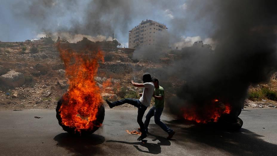 Manifestante palestino chuta um pneu em chamas durante confrontos com tropas israelenses em um protesto contra a ofensiva do país a Gaza, próximo a Ramallah, na Cisjordânia, em 18/07/2014