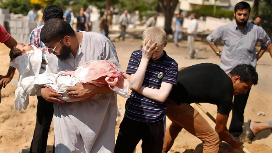 Palestinos enterram os corpos de duascrianças mortas durante ataque aéreo israelensesobre a Faixa de Gaza, em 24/07/2014