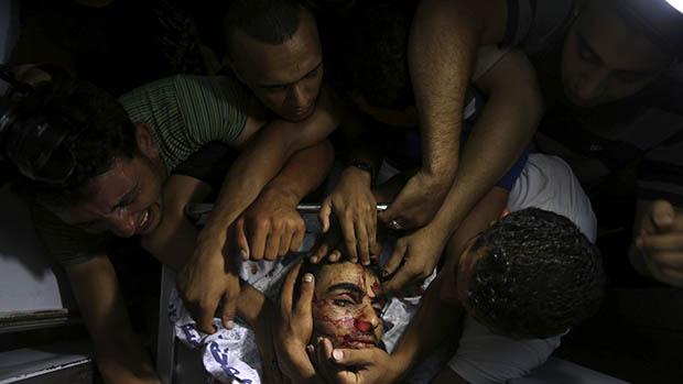 Pessoas choram em torno do corpo de um militante palestino na Faixa de Gaza, em 06/07/2014