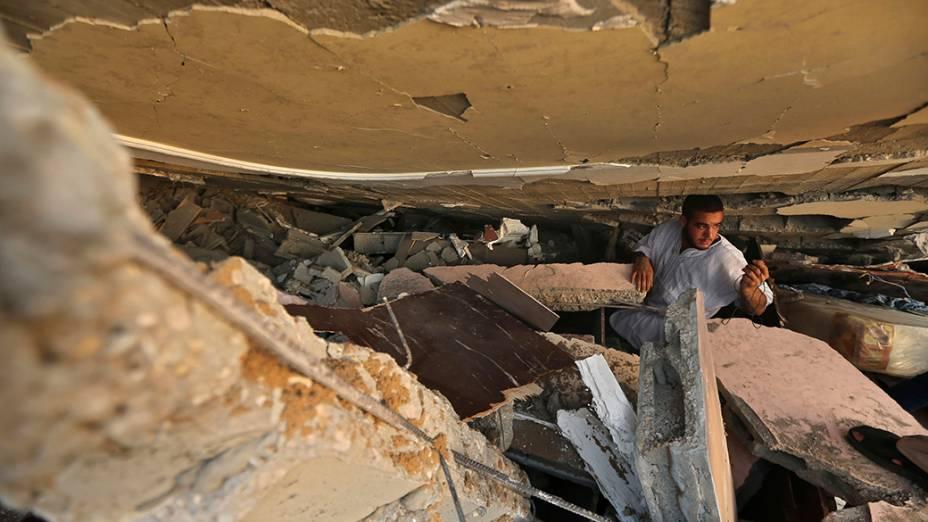 Homem palestino procura pertences sob os escombros de uma casa destruída em um ataque aéreo na cidade de Gaza, em 09/07/2014