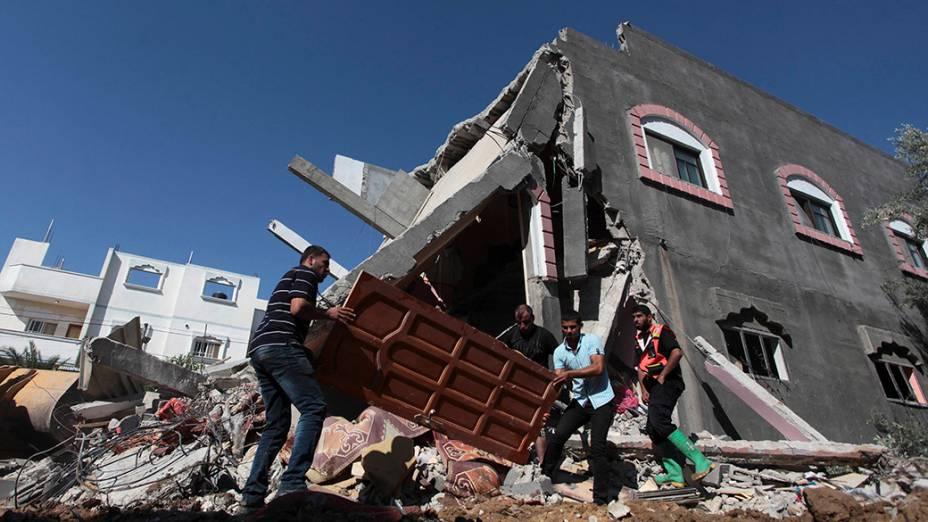 Palestinos carregam uma porta de uma casa destruída após um ataque aéreo no centro da faixa de Gaza, em 09/07/2014; Autoridadespalestinas informaram que pelo menos 37 pessoas foram mortas no enclave dominado pelo Hamas