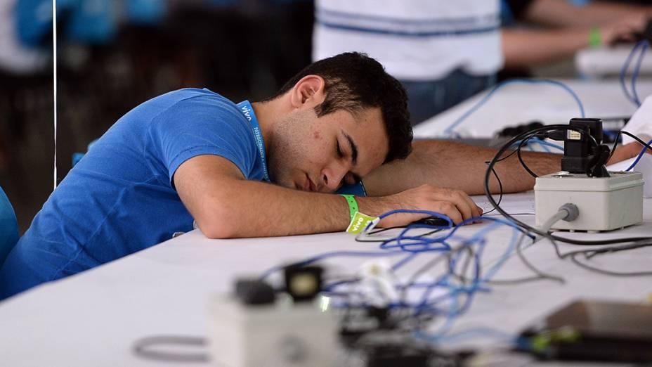 Participante descansa sobre a bancada na 7ª Campus Party, no Anhembi, em São Paulo