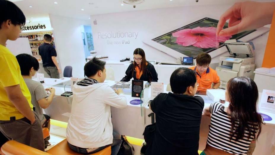 Vendedoras atendem consumidores na Apple Store para a venda de Ipad3, em Cingapura