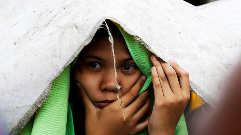 Menino tenta se proteger da chuva antes de embarcar em voo num avião militar usado para retirar pessoas atingidas em Tacloban