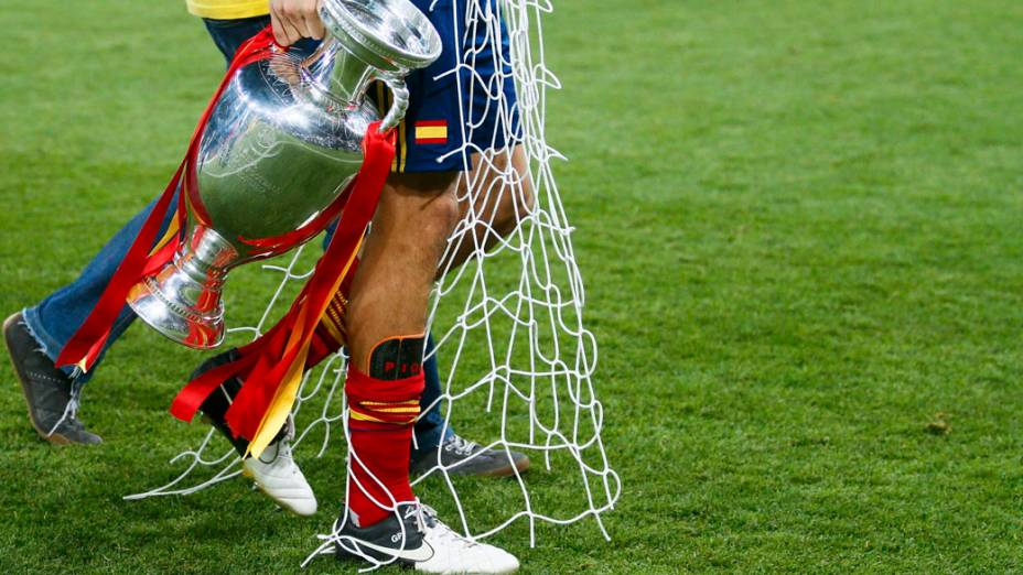 Espanhol Gerard Piqué carrega a taça e um pedaço da rede durante comemoração pelo título da Eurocopa 2012