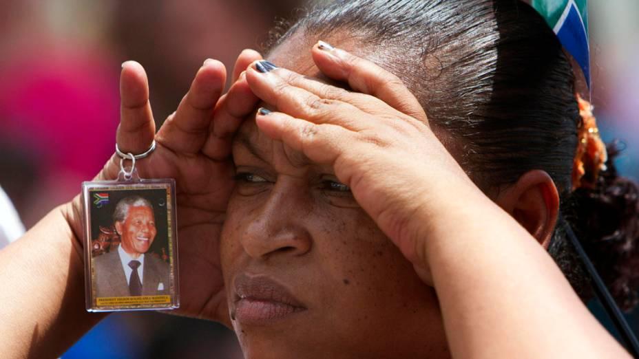Sul-africana assiste ao funeral de Nelson Mandela em um telão