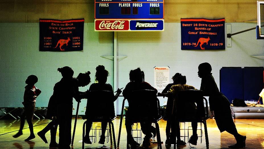 Crianças estudam em ginásio após a evacuação de suas casas, nos Estados Unidos
