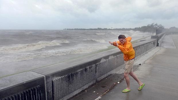 Morador de Nova Orleans enfrenta rajadas de vento às margens de lago
