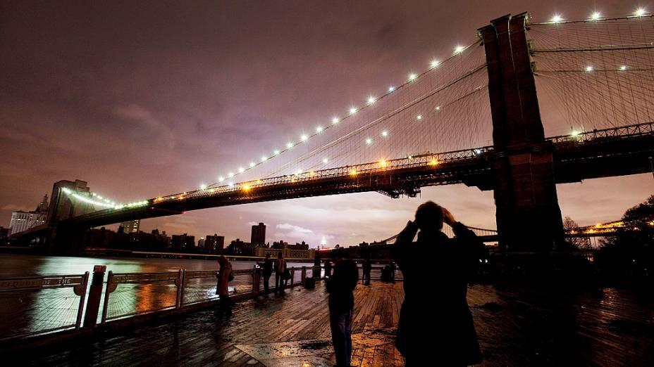 Pessoas fotografam a Ponte do Brooklyn após a passagem da tempestade Sandy