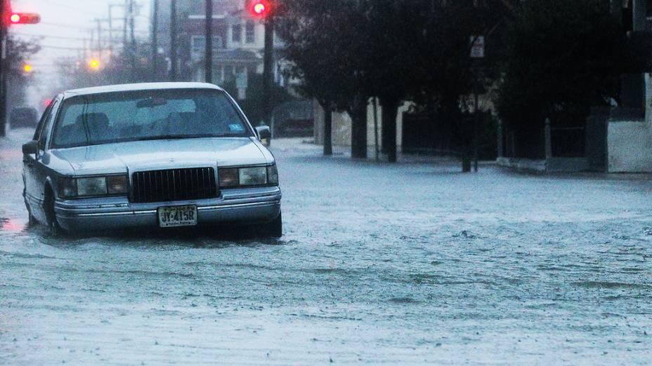 Mulher tira fotos de ondas provocadas pelo furacão Sandy em uma estrada de Southampton, Nova York