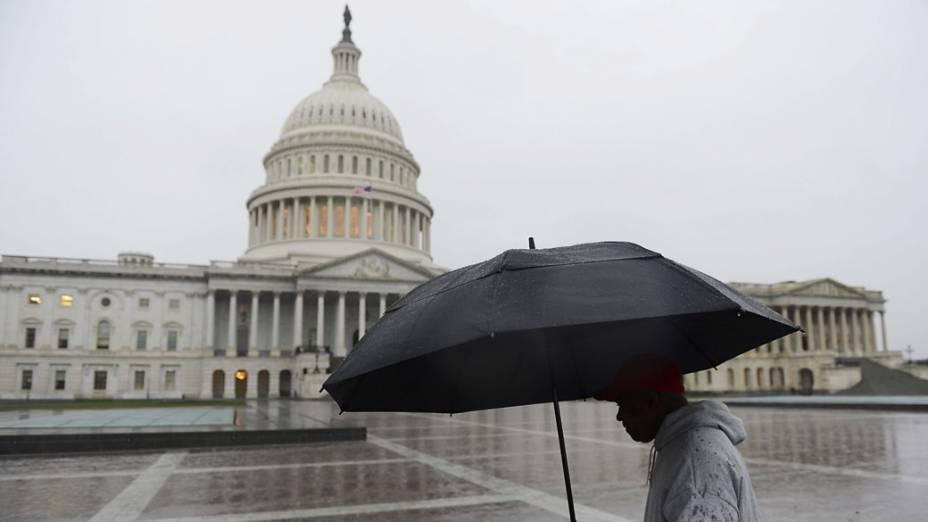 Homem se protege com guarda-chuva em frente ao Capitólio em Washington durante aproximação do furacão Sandy