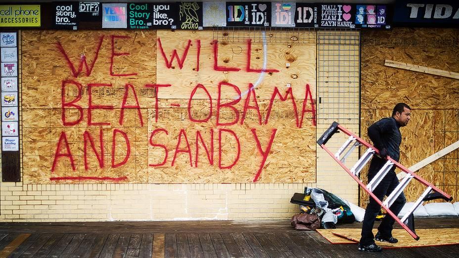 """Proteção de madeira em loja de Rehoboth Beach (EUA) traz mensagem política: """"Nós vamos vencer Obama e Sandy"""", em referência ao furacão que ameaça a região"""