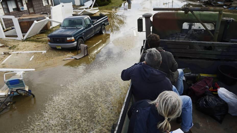 Pessoas resgatadas por veículos do exército, observam os danos causados pela tempestade Sandy em Nova Jersey