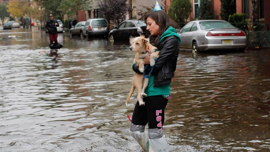 Mulher carrega seu cachorro em meio à enchente provocada pela tempestade Sandy em Hoboken, Nova Jersey