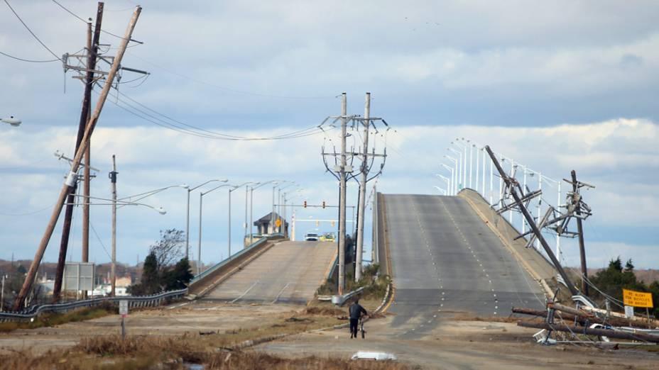 Homem passa entre postes derrubados pela passagem do furacão Sandy em Nova Jersey