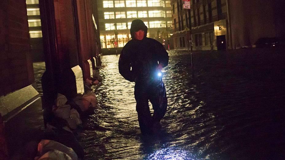 Segurança caminha em rua alagada e sem luz durante a madrugada no distrito financeiro de Manhattan, em Nova York