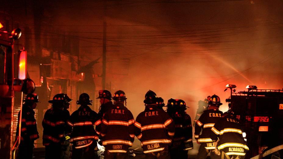 Bombeiros enfrentam dificuldade para combater um incêndio que destruiu 50 casas no bairro Queens, em Nova York