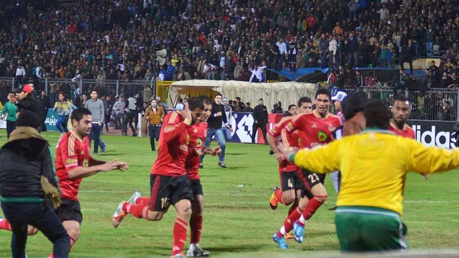 Jogadores saem do campo após torcedores invadirem o gramado durante a partida entre Al Masry e Al Ahly válida pelo Campeonato Egípcio